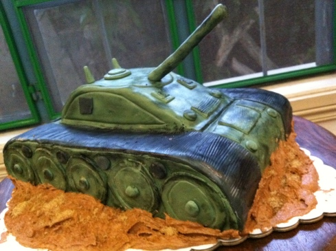 "Army Tank Cake nestled on top of buttercream icing ""mud"""